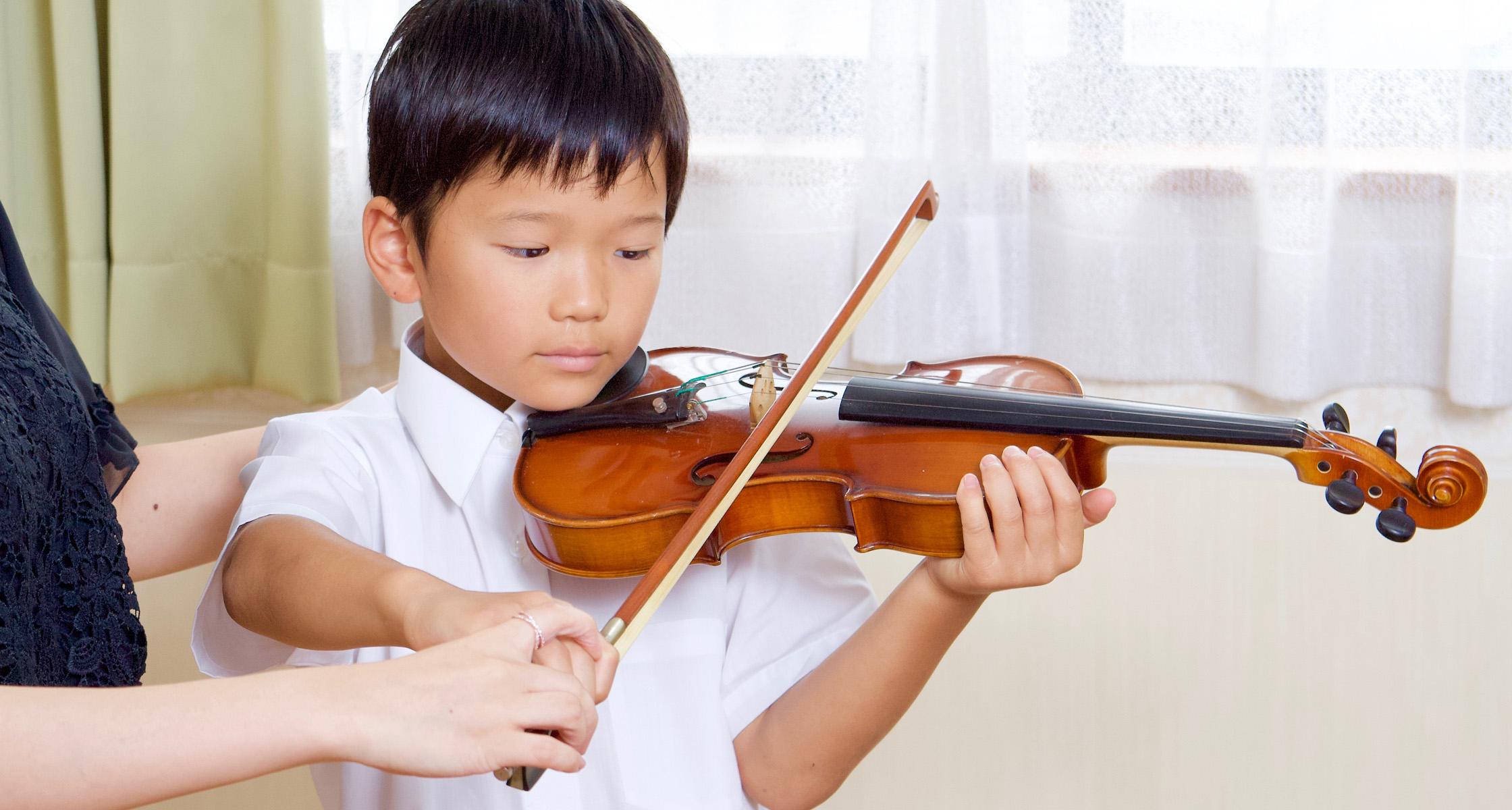 小学生がヴァイオリンを弾いている